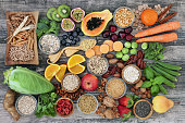 High dietary fibre health food concept with fruit, vegetables, whole wheat pasta, legumes, cereals, nuts and seeds  with foods high in omega 3, antioxidants, anthocyanins, smart carbohydrates and vita