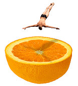 High diving swimmer in swim suit briefs jumping down in a half fresh juicy orange fruit like a swimming pool - manipulated photo concept image - isolated on white