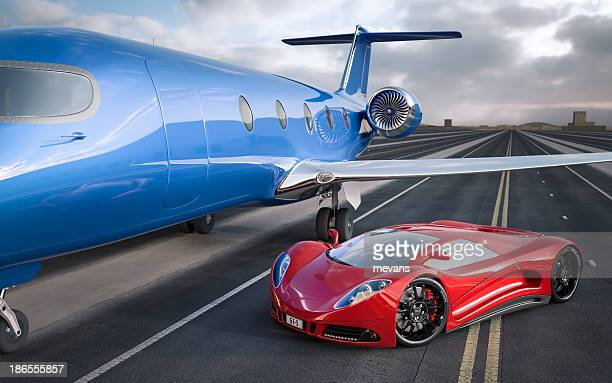 A high end red sports car next to a jet for luxury travel