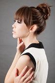 High fashion: profile of an elegant asian model on grey