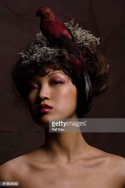 High fashion woman with conceptual bird's nest atop head