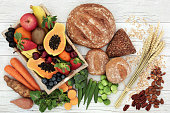 High fiber health food concept with fresh fruit, vegetables, wholegrain bread, nuts and cereals. Foods high in antioxidants, anthocyanins, omega 3 fatty acids and vitamins. Rustic background, top view