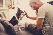 Young man and his dog giving high five to one another