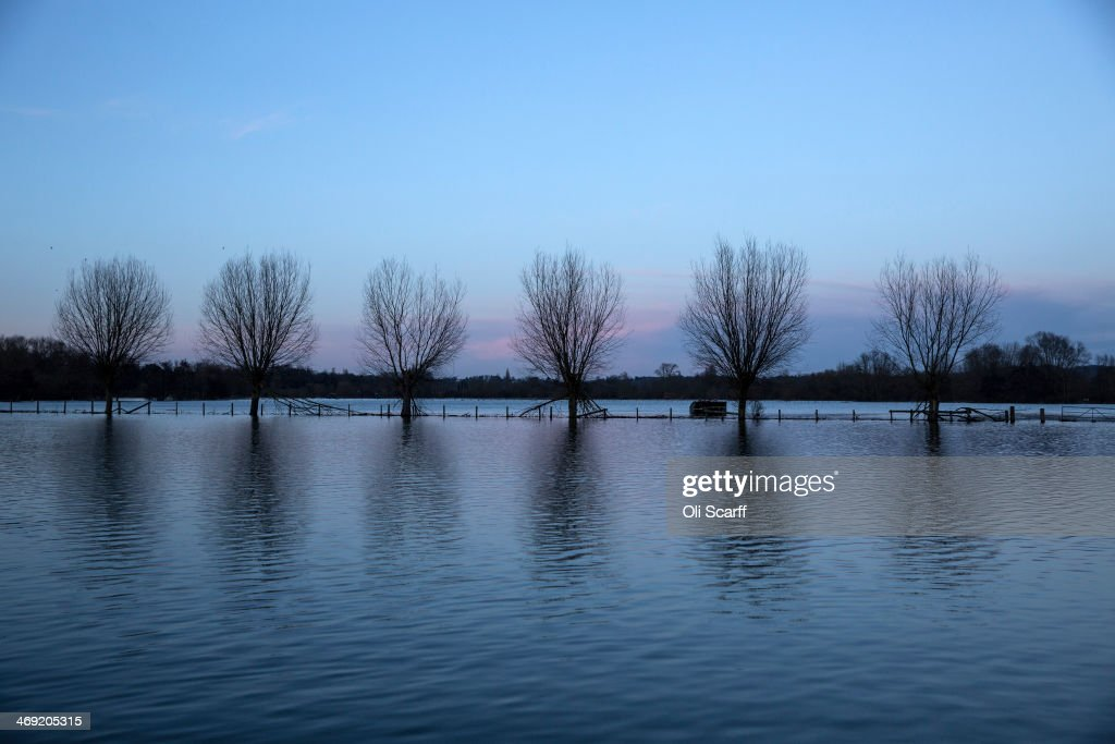 High flood waters partially submerge trees in a field near the river Thames on February 13, 2014 in Wargrave, England.The Environment Agency continues to issue severe flood warnings for a number of areas on the River Thames in the commuter belt west of London. With heavier rains forecast, people are preparing for the water levels to rise.