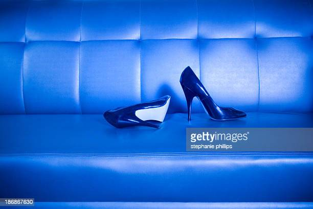 High Heel Shoes Lying on a Sleek Leather Couch