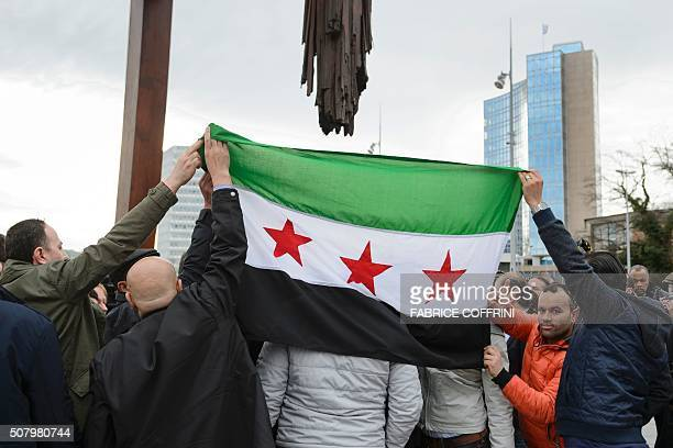 High Negotiations Committee supporters hold a Syrian flag during a press conference on Syrian peace talks at the Place des Nations outside of the...
