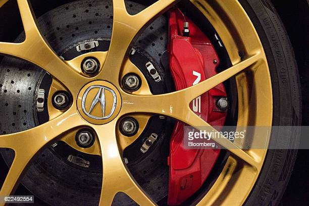 High performance disc brakes are seen through the wheel of a Honda Motor Co 2017 Acura NSX vehicle at the Honda Auto Plant in Marysville Ohio US on...