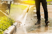 High pressure deep cleaning Worker cleaning driveway with gasoline high pressure washer,sunlight background.