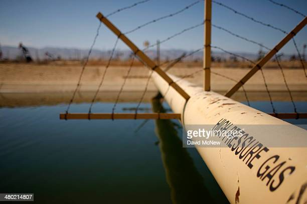A high pressure gas line crosses over a canal in an oil field over the Monterey Shale formation where gas and oil extraction using hydraulic...