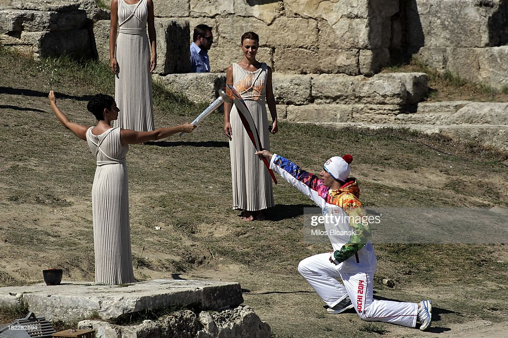 High Priest Ino Menegaki lights the torch of a torchbearer during the lighting ceremony of the Olympic Flame for the Sochi 2014 Winter Olympic Games at Ancient Olympia on September 29, 2013 in Olympia, Greece.