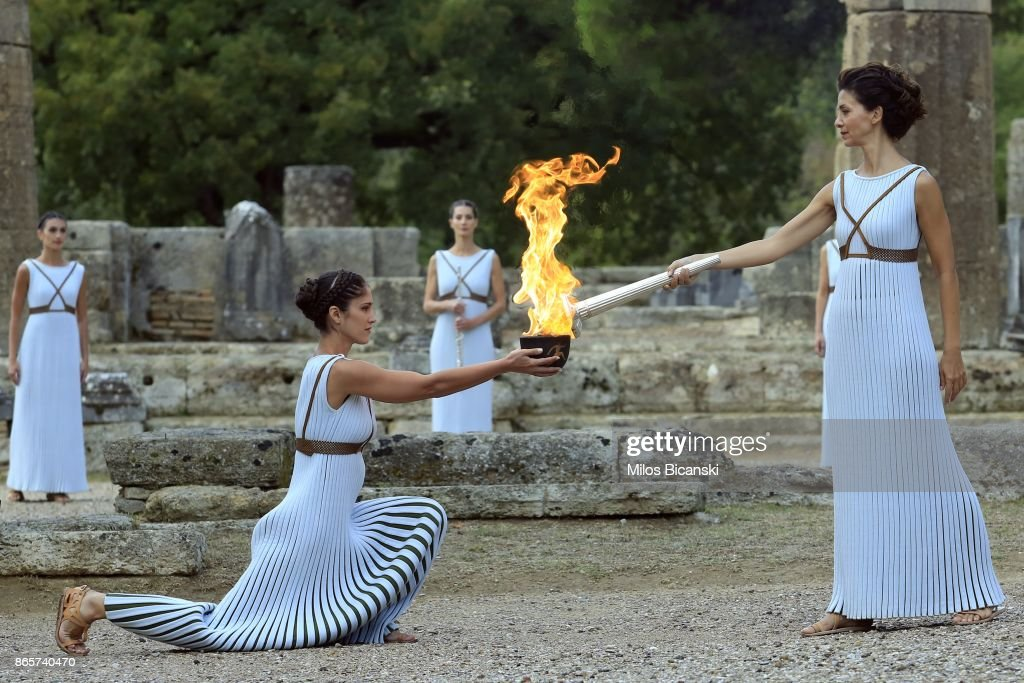 flame lighting olympics. high priestess passes the olympic flame at temple of hera during a lighting ceremony olympics