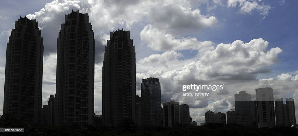 High rise buildings stand against a backdrop of clouds in Jakarta on December 27, 2012. According to projections by the World Bank, Indonesia's major trading partners are estimated to grow by 3.3 per cent by the end of the year and by a slightly higher 3.6 per cent in 2013, which will improve the prospects for higher export growth.