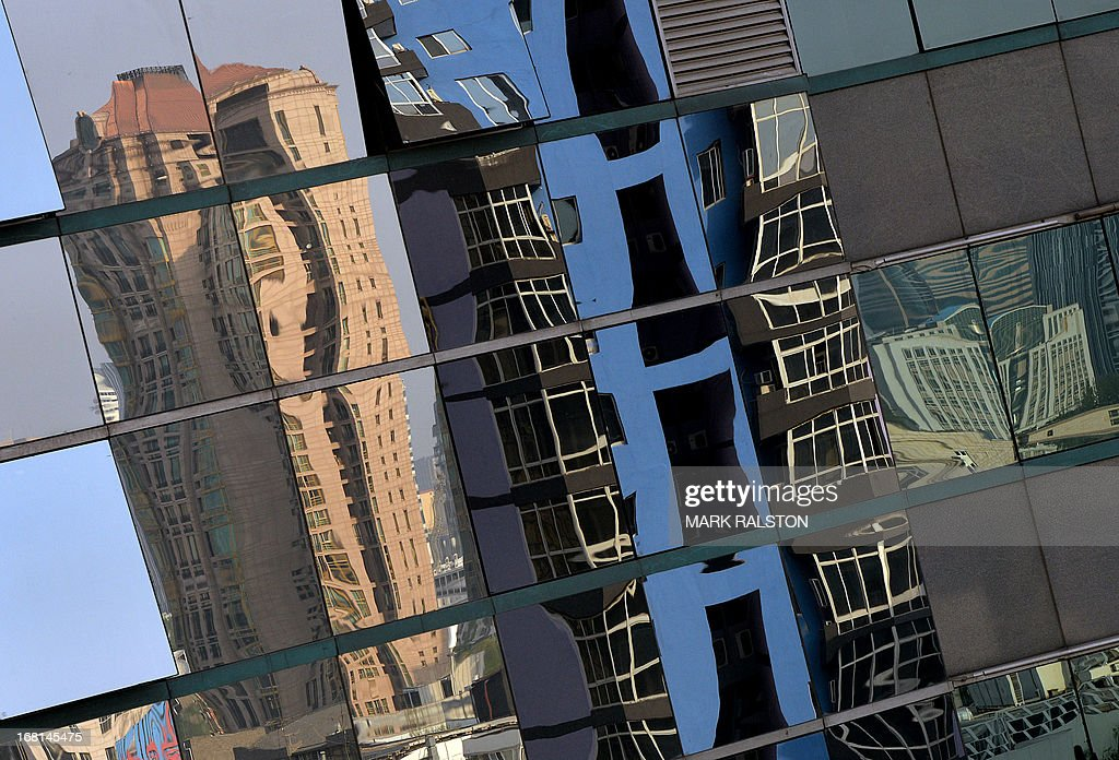 High rise properties are reflected on an office building's windows in Beijing on May 6, 2013. Chinese home prices picked up in April in their fifth consecutive monthly rise and the cost of a new home in 100 major cities rose 5.3 percent year-on-year to an average 10,098 yuan (USD 1638) per square metre, said the China Index Academy. AFP PHOTO/Mark RALSTON