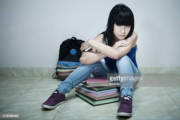 高校アジアの女の子スチューデント床に座る、ブックです。