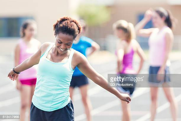 High school athlete stretches as she prepares for race