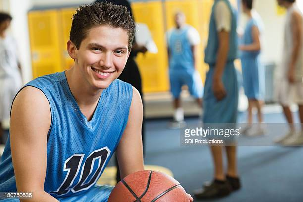 High school basketball player in locker room after winning game