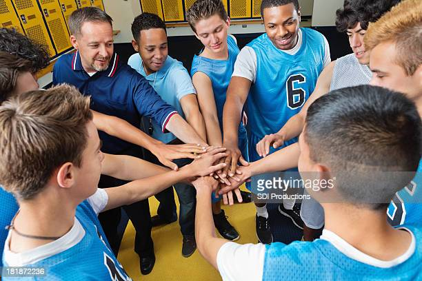 High school basketball team huddled in locker room before game