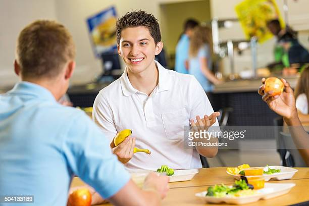 High school boy eating lunch with friends in cafeteria