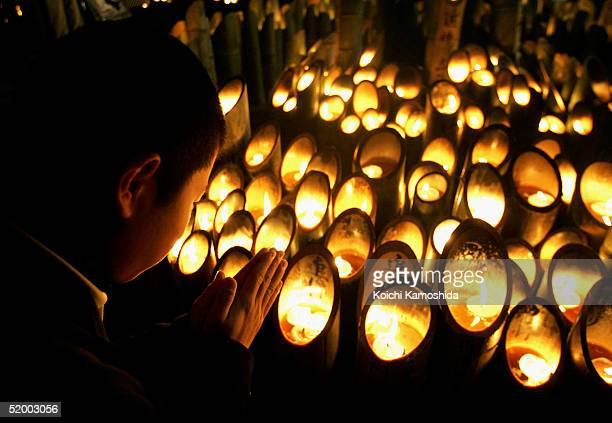 High school boy lights a candle to offer a prayer for victims during a memorial service to commemorate the 10th anniversary of the 1995 earthquake in...