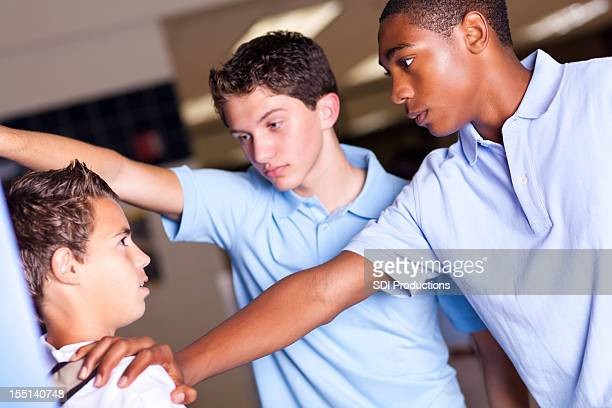 High school boys bullying a smaller student