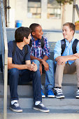 Group Of Male Teenage Pupils Outside Classroom Looking At Each Other Talking