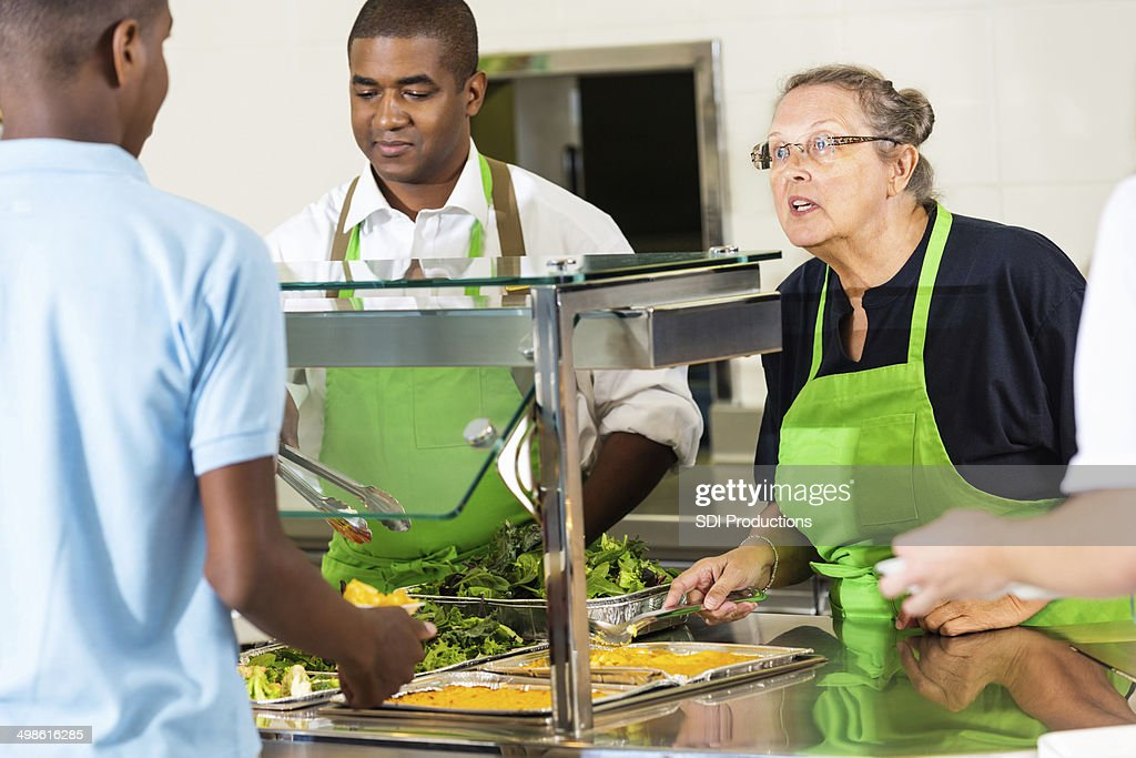 High school cafeteria lunchroom workers serving hot meal to students