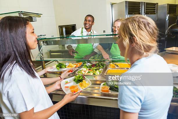 High school cafeteria workers serving healthy lunch options to students