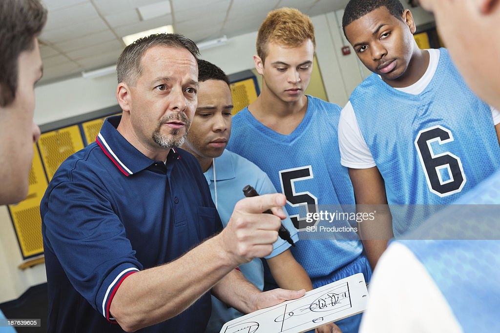 High school coach instructing basketball players in locker room : Stock Photo