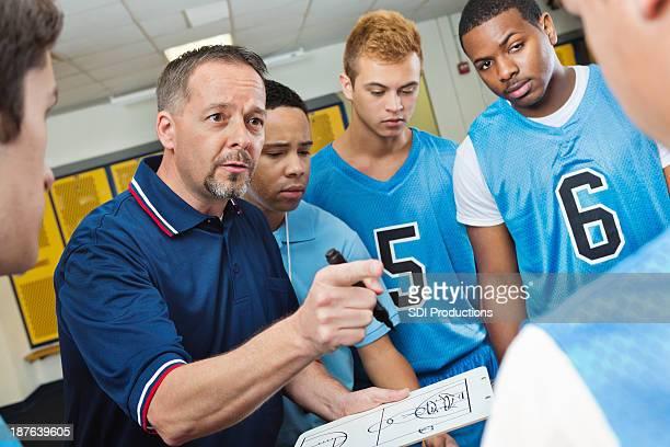High school Treinador instruir os jogadores de basquetebol no Vestiário