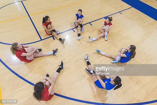High school female volleyball players warming up together
