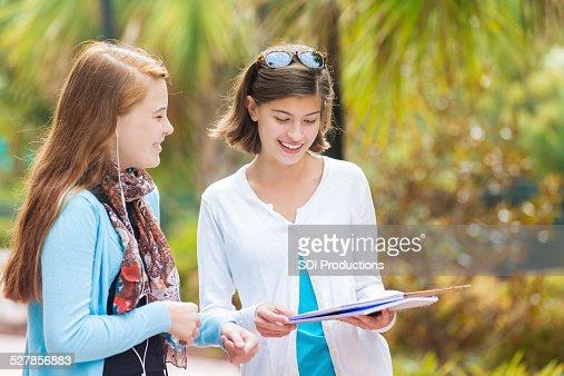 High school freshmen comparing homework notes after class