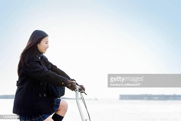High school girl cycling by the ocean