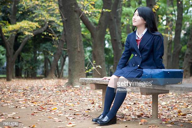 High school girl sitting in park