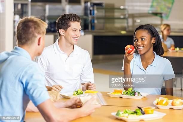 High school girl talking with friends eating healthy cafeteria lunch