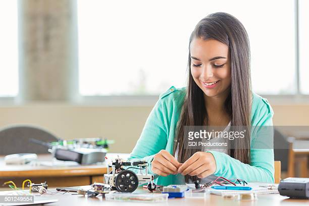 High school girl using kit to build small robot