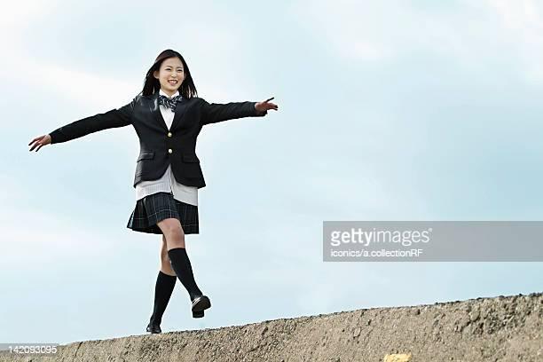High school girl walking on top of a breakwater