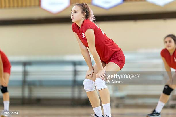 High school girl with hands on knees returning volleyball serve