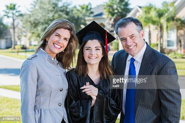 High school graduate posing with her parents