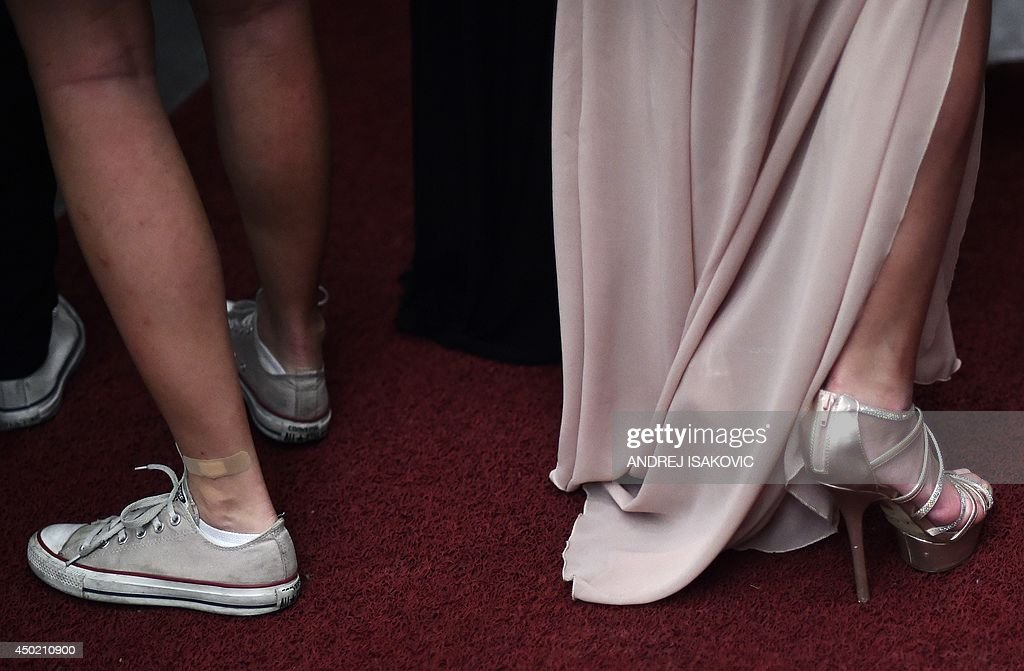 A high school graduate wearing high heels arrives to her prom night next to a girl wearing Converse shoes, in the Serbian capital of Belgrade on June 6, 2014.