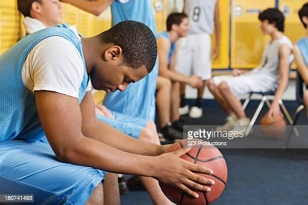 High school locker room with basketball team players