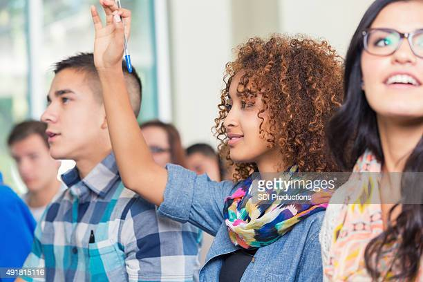 High school or college student raising hand to ask question