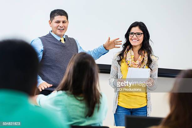 High school professor introducing student, reading report to class