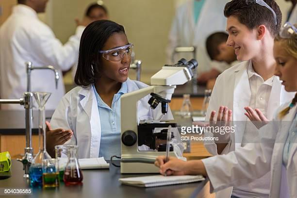 Lycée science lab partenaires commerciaux discuter de la production et à l'aide de microscope