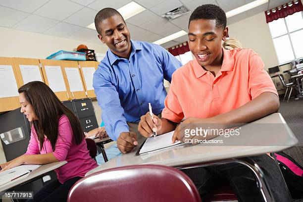 High school student checking student's assignment in classroom
