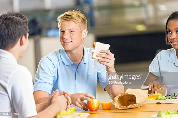 High school student eating brown bag lunch in cafeteria