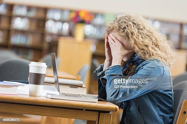 High school student frustrated while studying after hours in library
