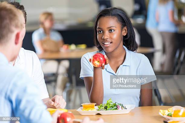 High school student having lunch with friends in cafeteria