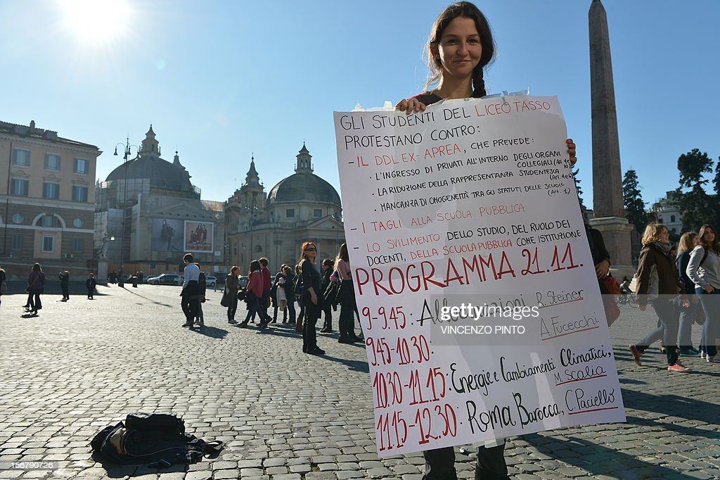 A high school student holds a placard reading ' The students of the Tasso high school protest against...the budgets cuts...' and showing the programme of the lessons to be given on Piazza del Popolo by teachers supporting their demonstration on November 21, 2012 in Rome. Students at the Tasso high school in Rome have occupied their school and taken their lessons to the public squares of the eternal city in protest over government budget cuts to education and high youth unemployment.