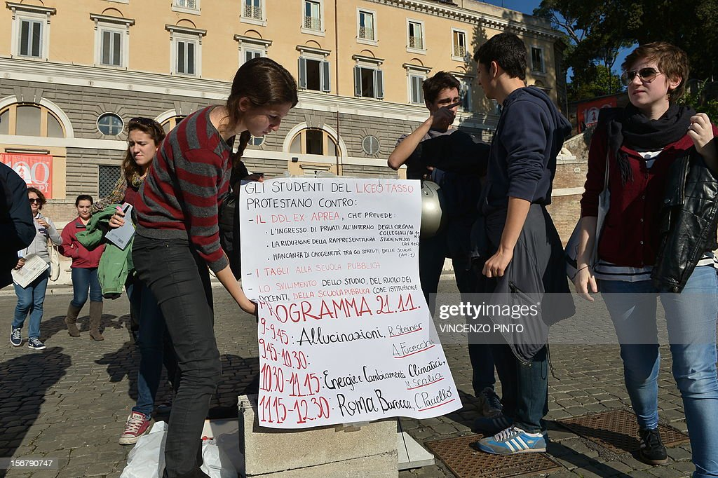 A high school student holds a placard reading ' The students of the Tasso high school protest against...the budgets cuts...' and showing the programme of the lessons to be given on Piazza del Popolo by teachers supporting their demonstration on November 21, 2012 in Rome. Students at the Tasso high school in Rome have occupied their school and taken their lessons to the public squares of the eternal city in protest over government budget cuts to education and high youth unemployment. AFP PHOTO / VINCENZO PINTO