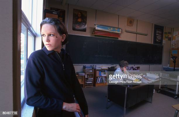 High school student standing by window in classroom